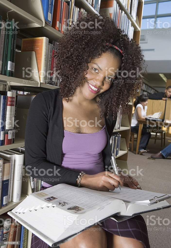 Student Taking Notes in the Library stock photo