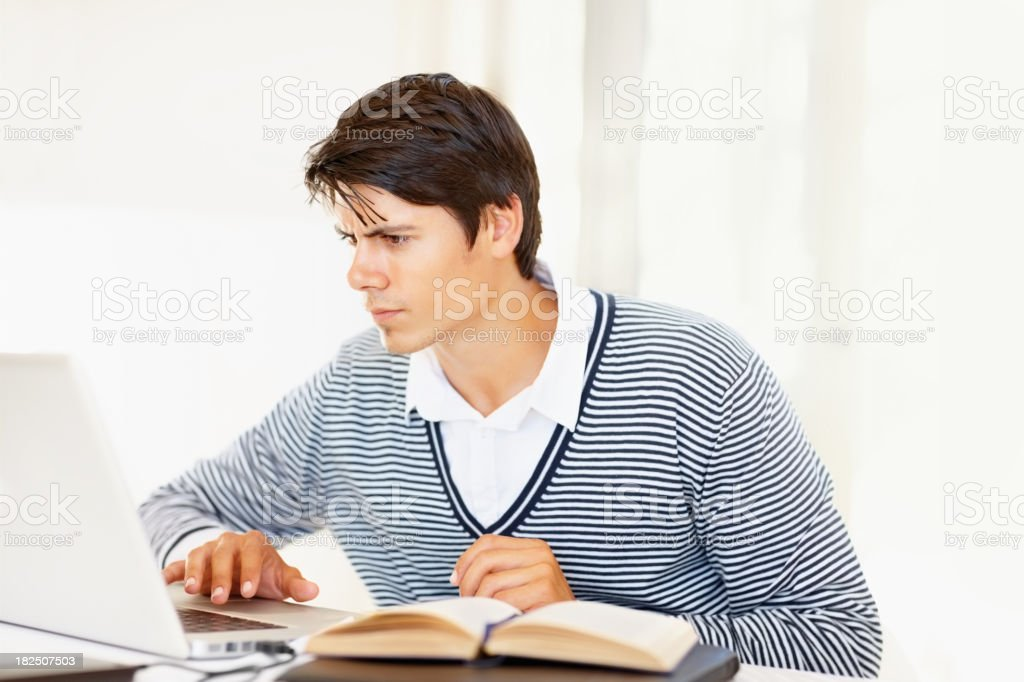 Student using a laptop to do his homework royalty-free stock photo