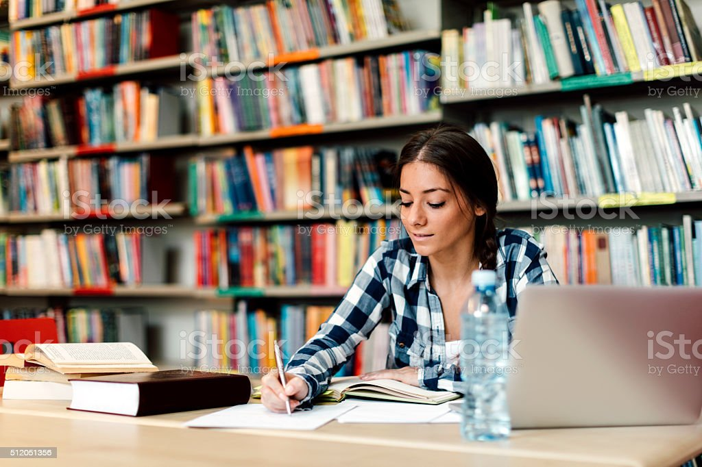 Student using laptop for taking notes to study stock photo