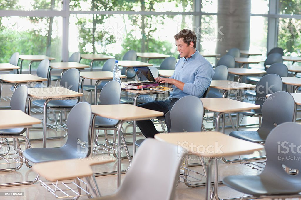 Student using laptop in classroom stock photo