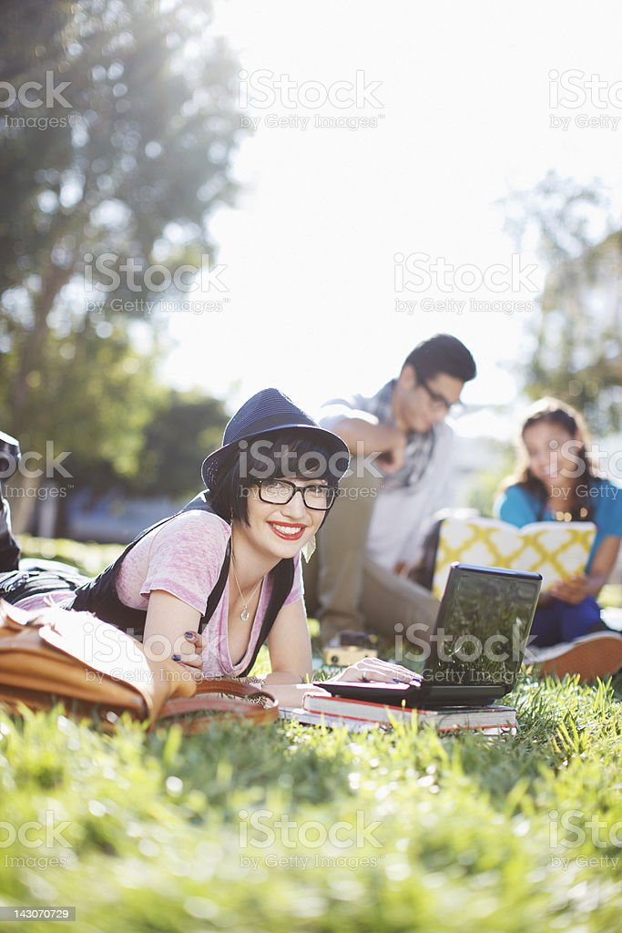 Student using laptop in grass outdoors stock photo