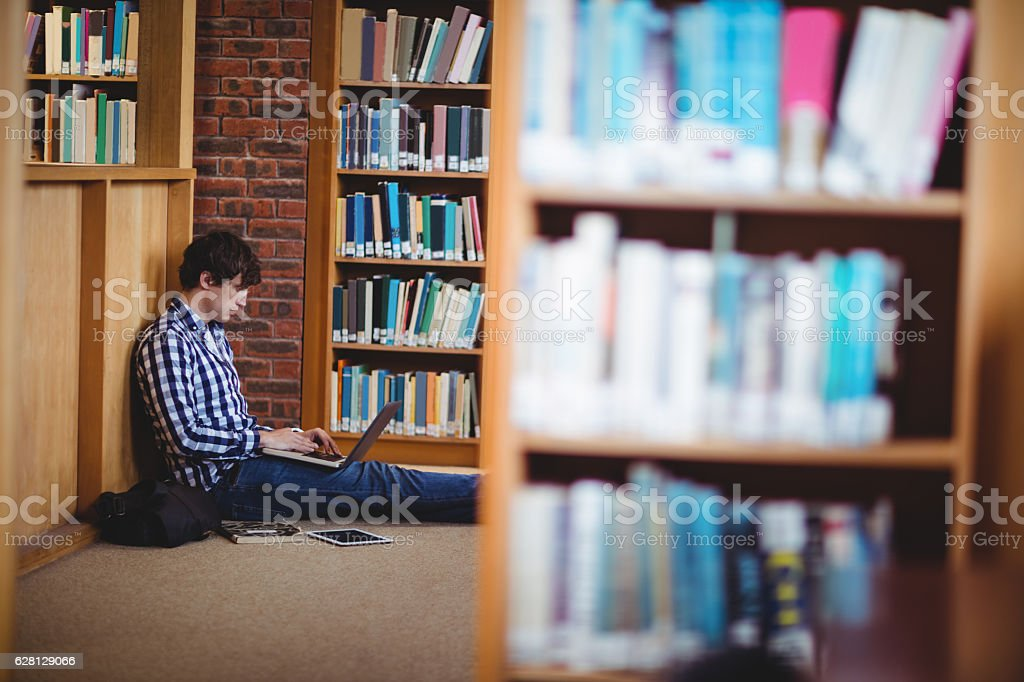 Student using laptop in library stock photo
