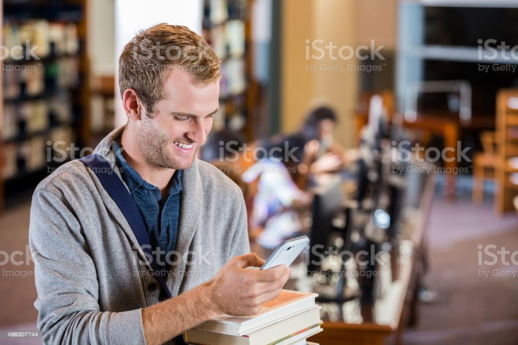 Student using smart phone while checking out books from library stock photo