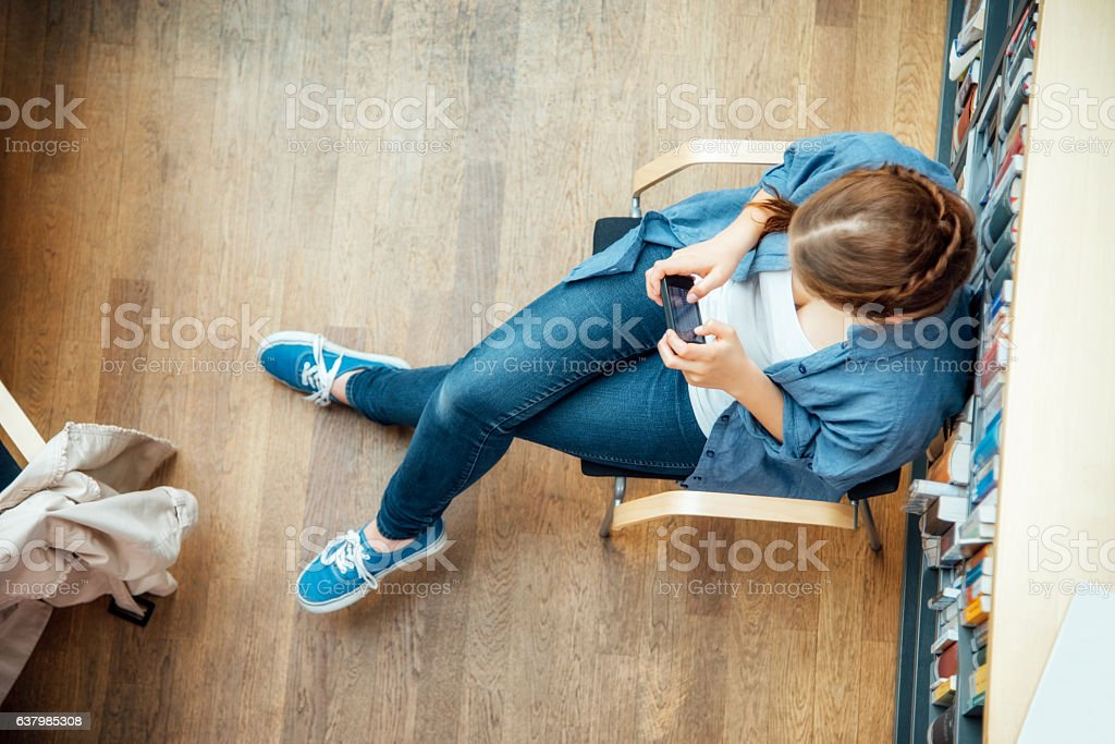 student using smart phone while sitting against bookshelf in classroom stock photo