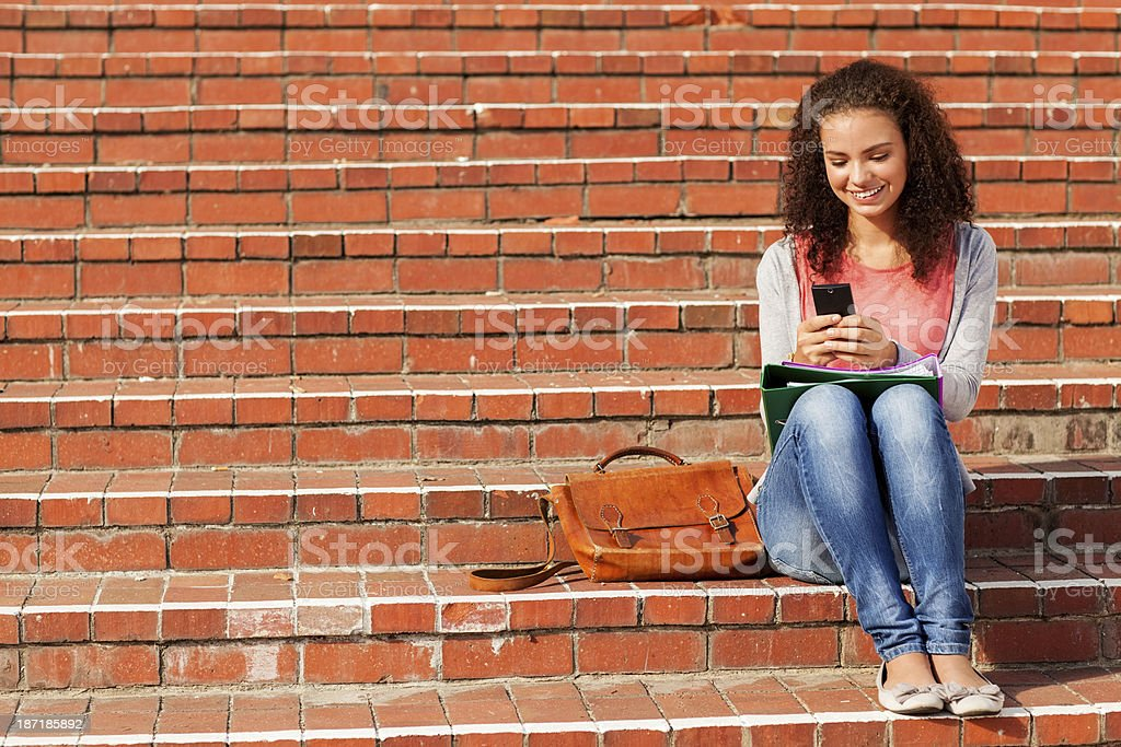 Student Using Smart Phone While Sitting On Steps At Campus royalty-free stock photo
