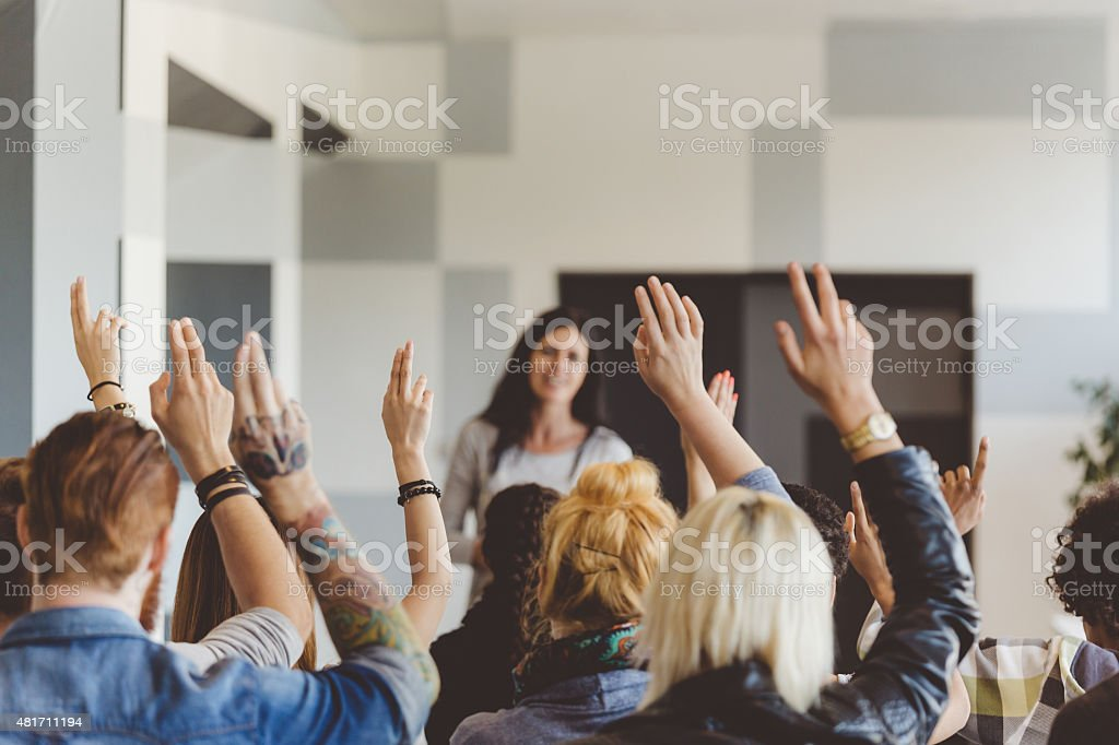 Student voting on seminar, raising hands stock photo