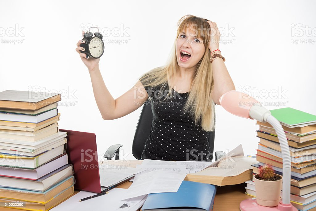 student with an alarm clock in hands understand stock photo