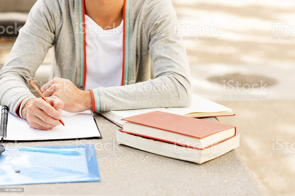 Student With Books And Pen Sitting At Table On Campus royalty-free stock photo