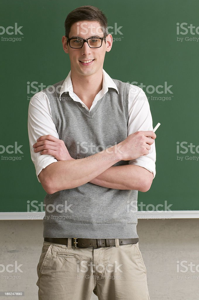 student with crossed arms at blackboard stock photo