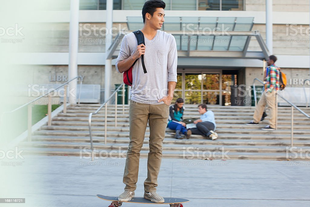 Student with skateboard on campus stock photo