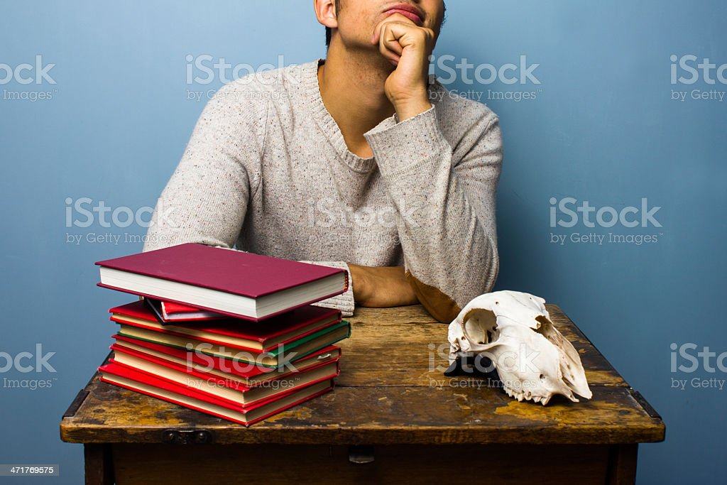 Student with skull and books is contemplating royalty-free stock photo