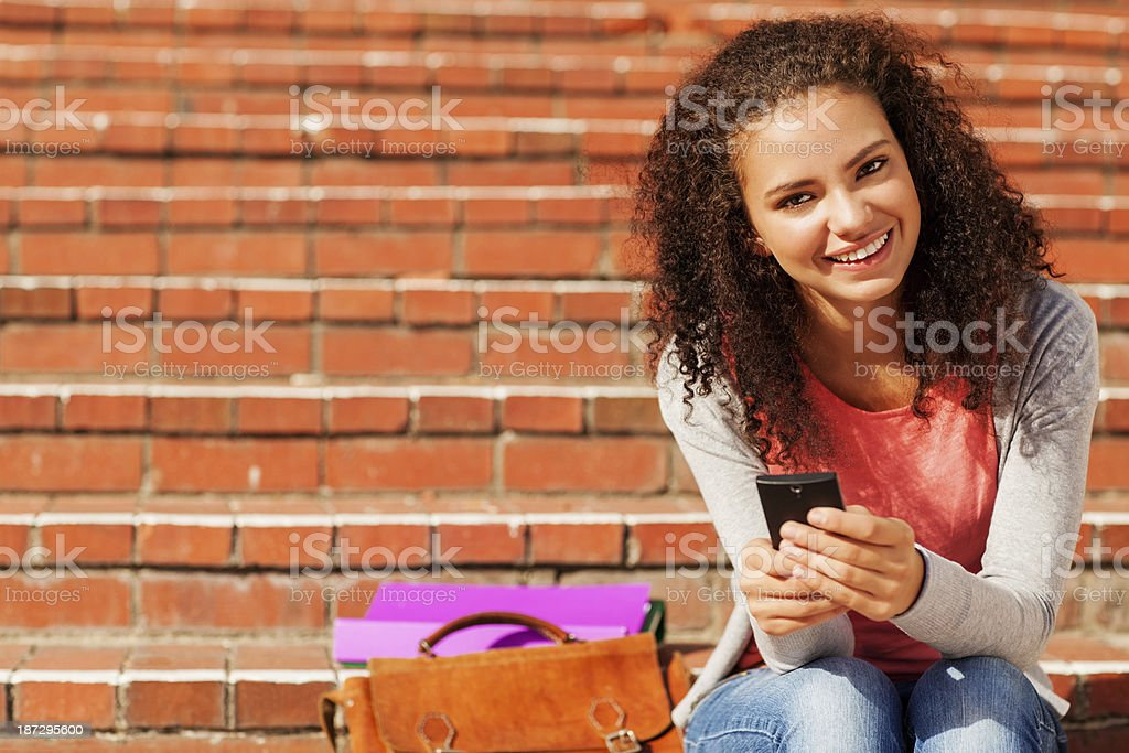 Student With Smart Phone; File And Bag Sitting On Steps royalty-free stock photo