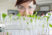 Student with tray of test tubes holding seedlings