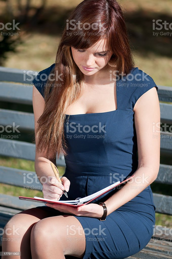 Student woman reviewing diary at city park stock photo