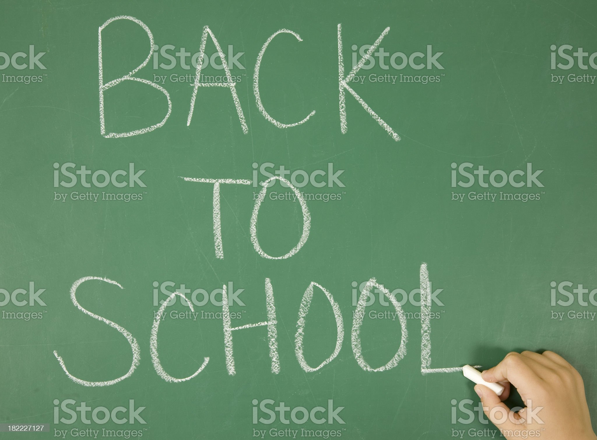 Student Writing Back to School on Chalkboard royalty-free stock photo
