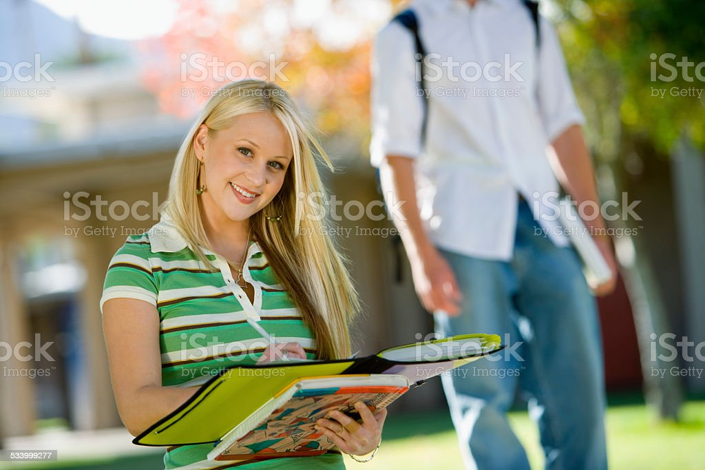 Student Writing in Notebook Outside stock photo