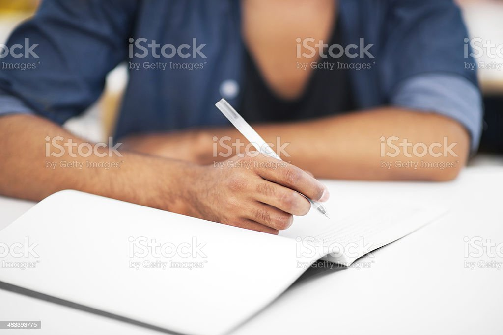 Student writing in notebook. stock photo