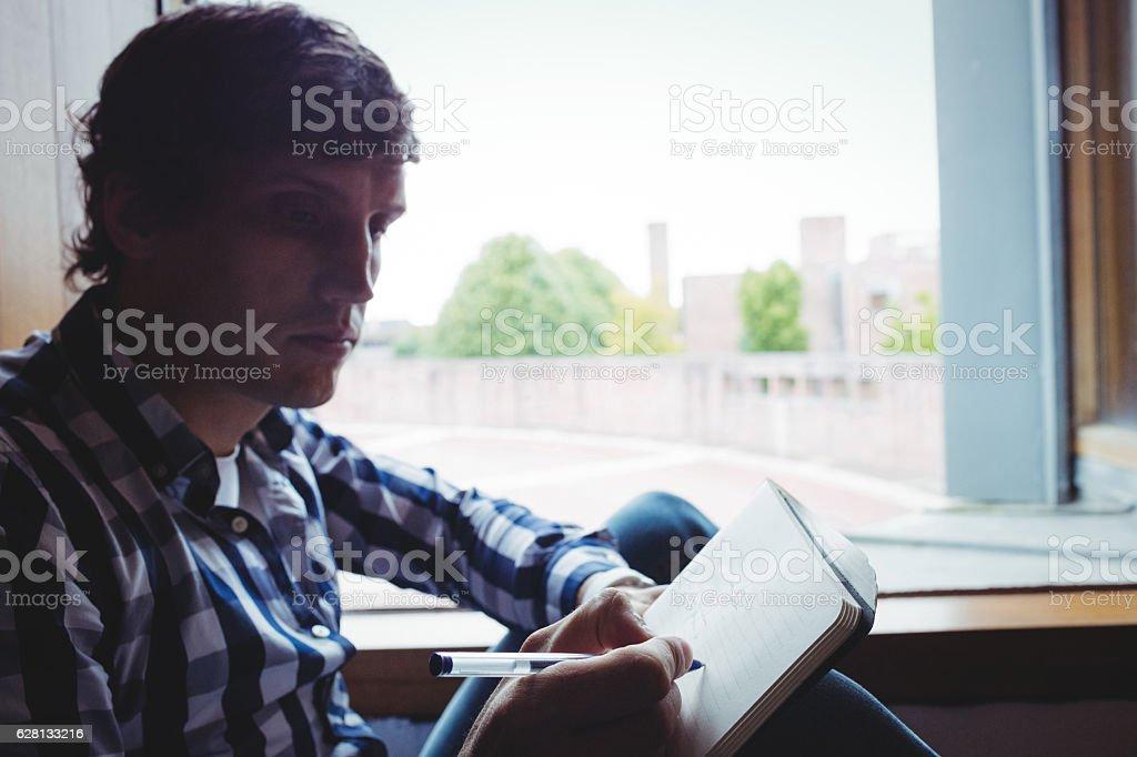 Student writing notes near window stock photo
