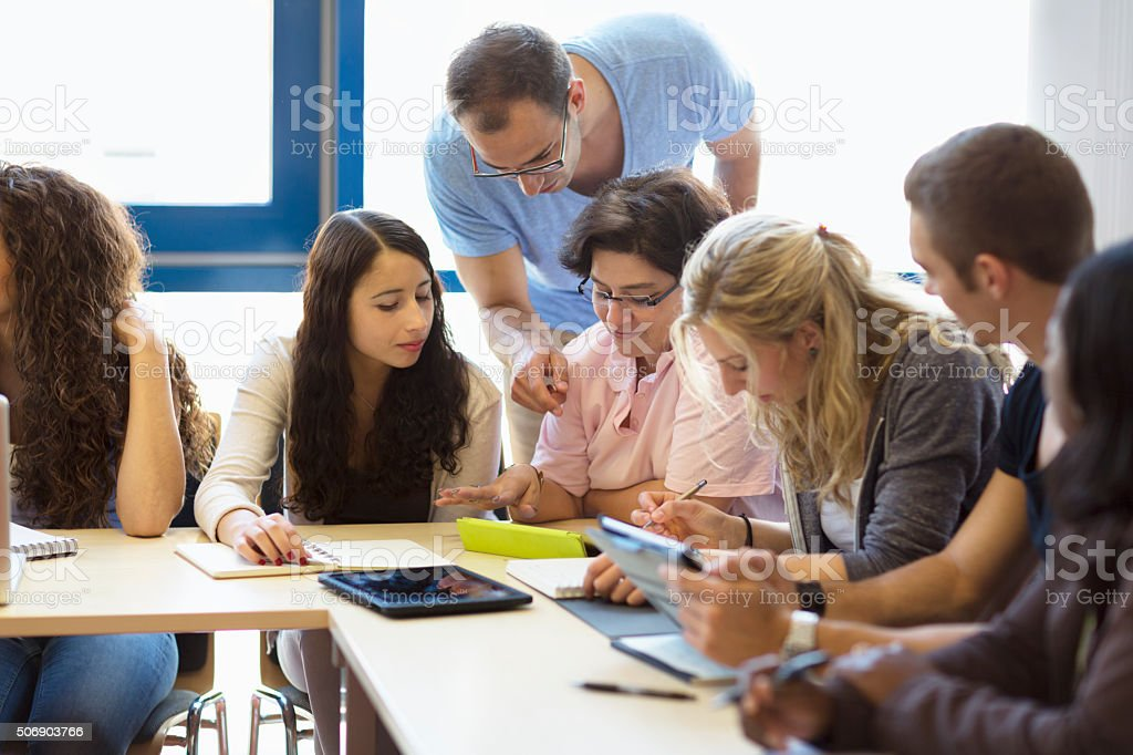 students and teacher  in classroom working with digital tablet stock photo