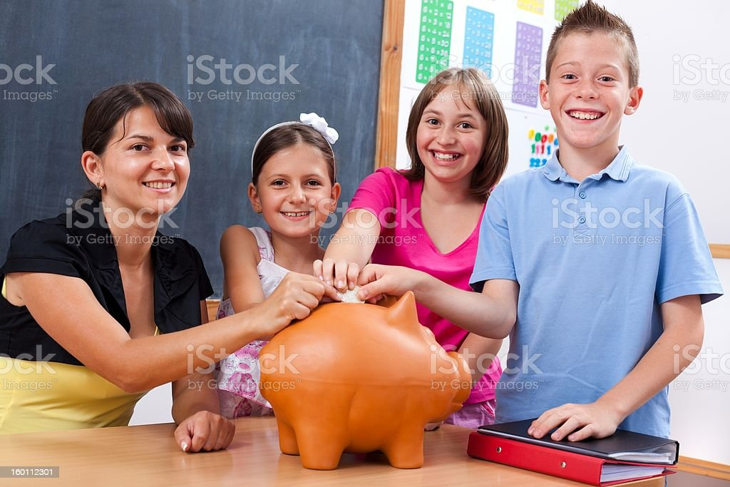 Students and teacher putting coin into piggy bank royalty-free stock photo