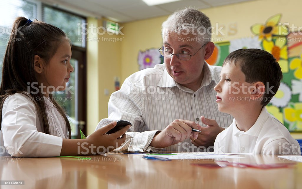 students are working with their teacher on a math project royalty-free stock photo