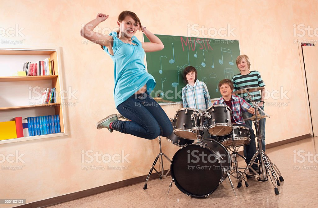 Students at music class girl jumping smiling  boy playing drums stock photo