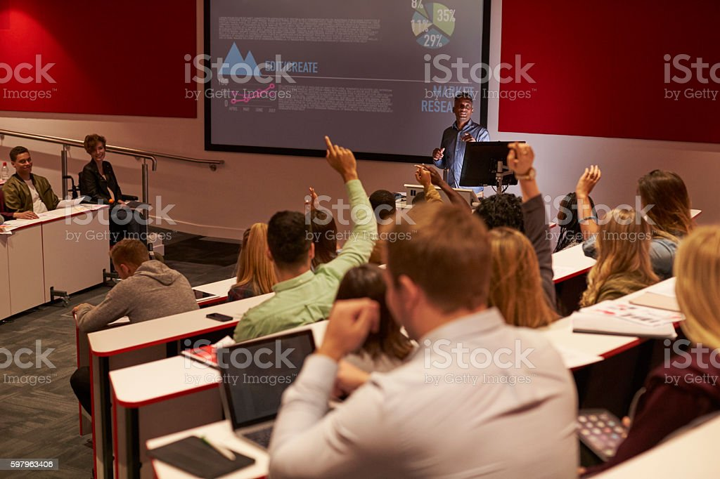 Students at university lecture raise hands to ask questions stock photo
