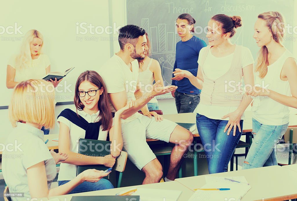 students chatting while sitting in the room stock photo