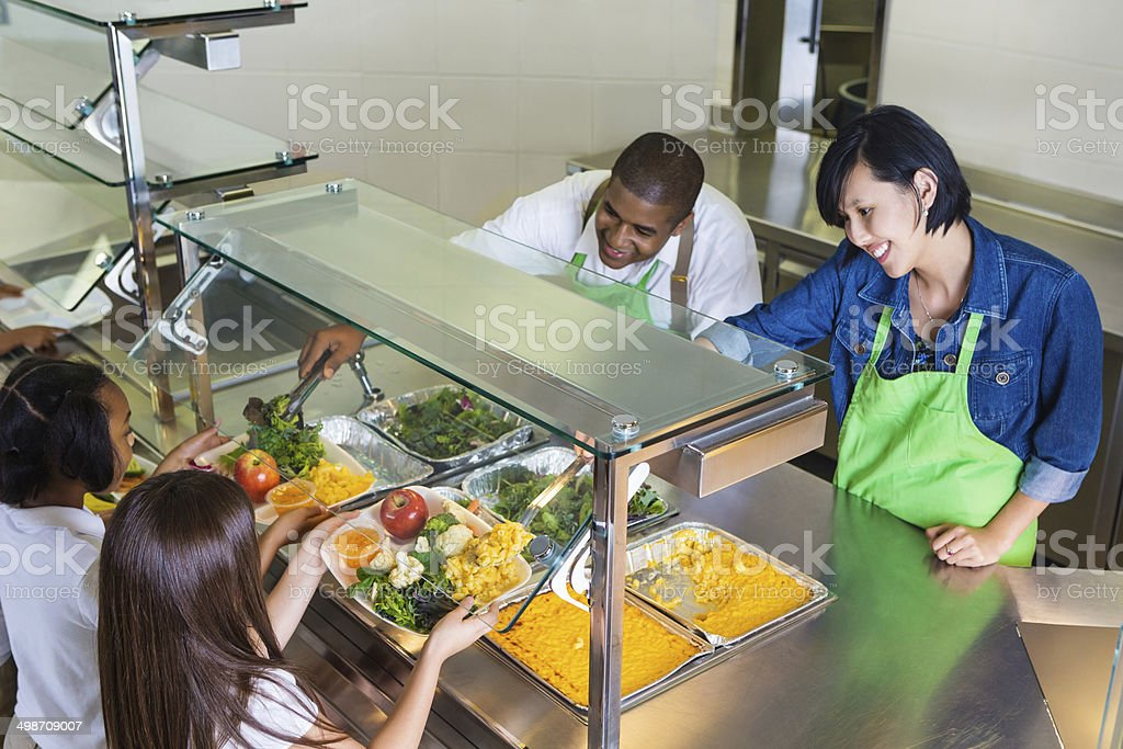 Students choosing healthy food in school cafeteria lunch line stock photo