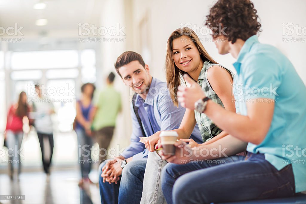 Students communicating on a break in school corridor. stock photo