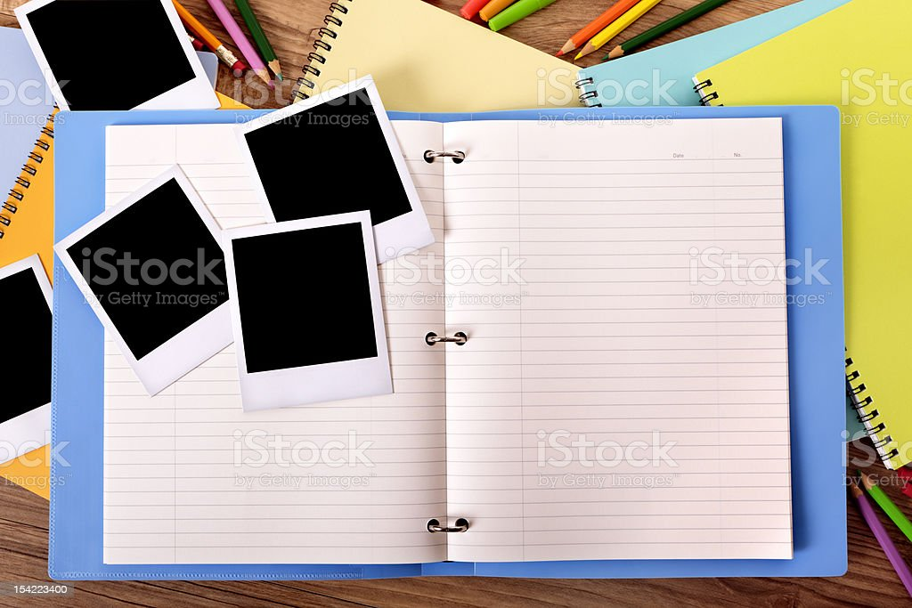 Student's desk with blue project folder and blank photos. royalty-free stock photo