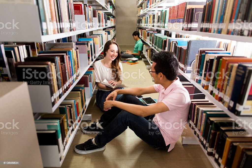 Students flirting in the library stock photo