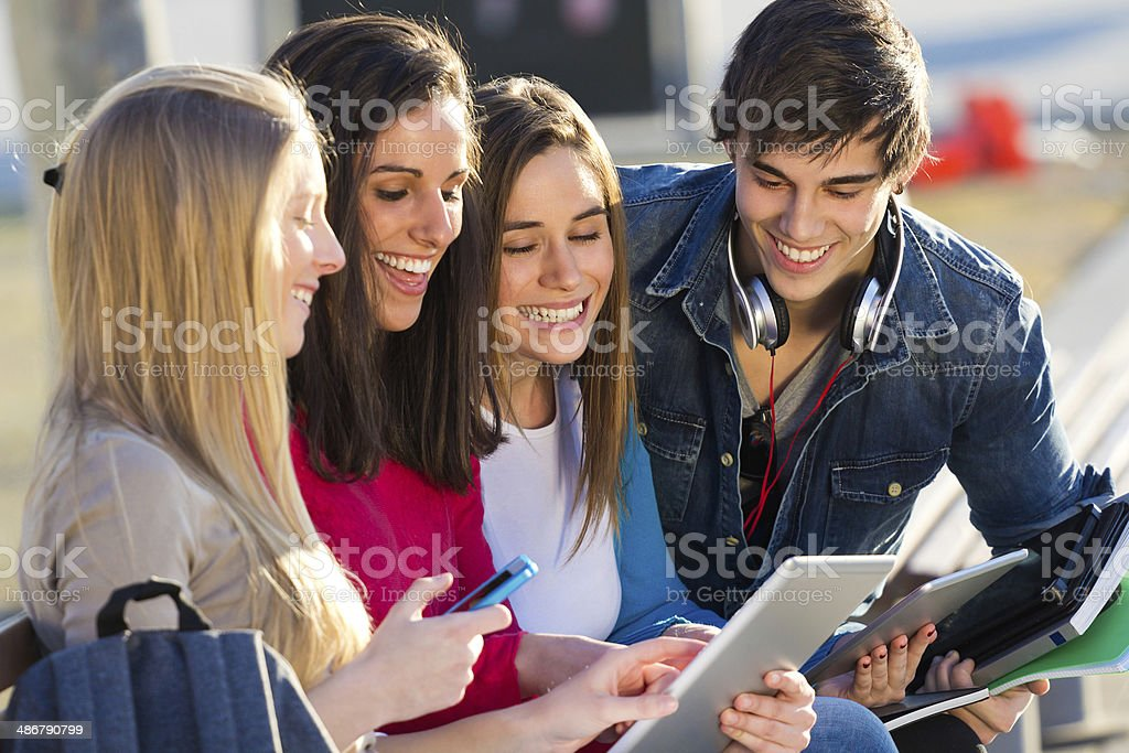 Students having fun with smartphones and tablets after class stock photo