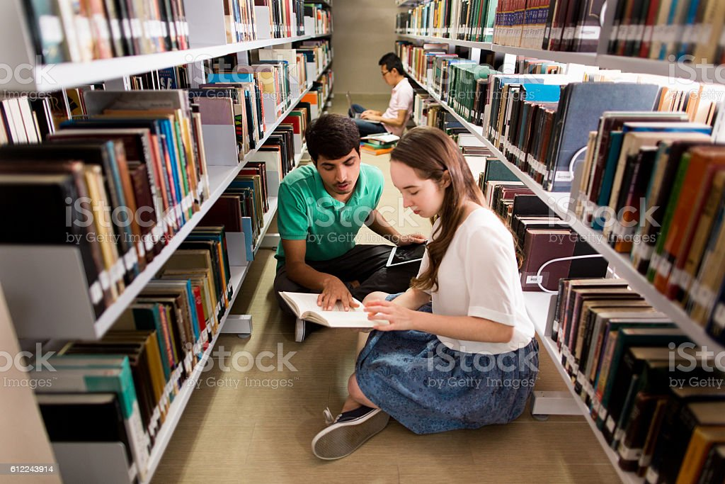 Students helping each other in the library stock photo