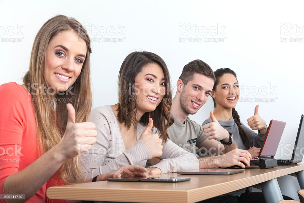 Students hold thumbs up stock photo