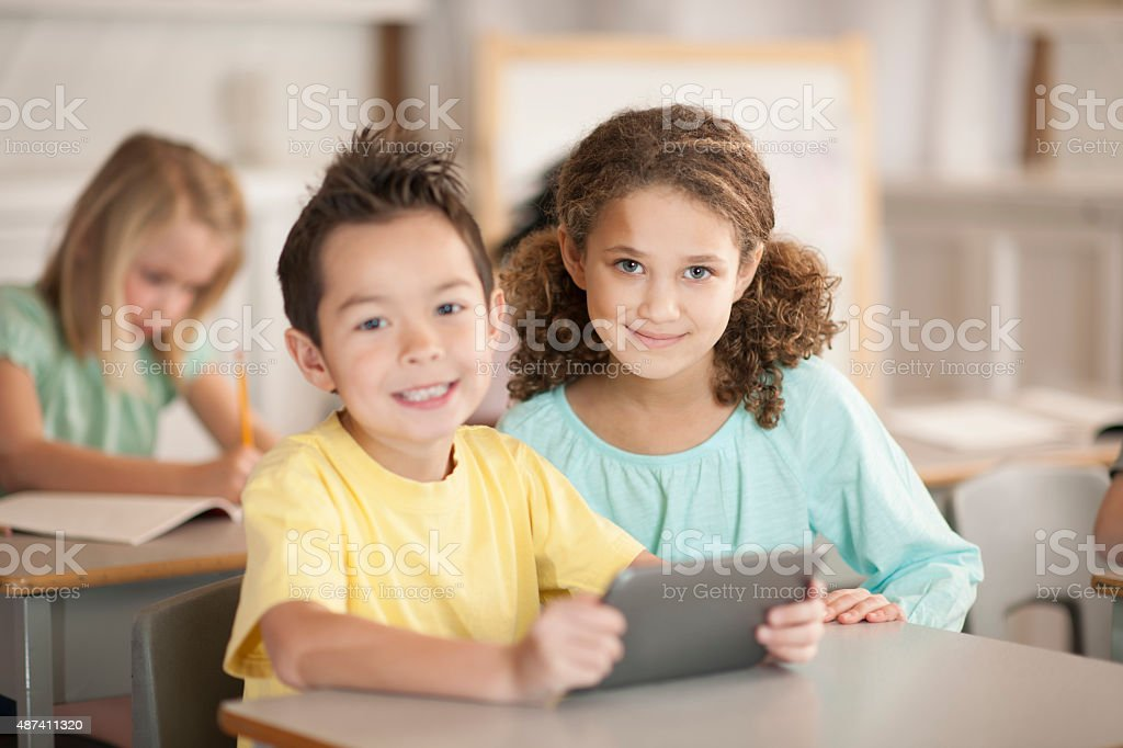 Students Holding a Tablet in Class stock photo