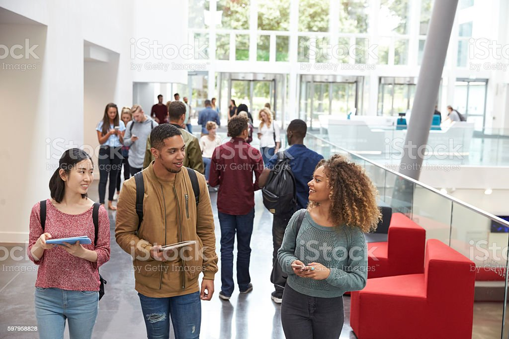 Students holding tablets and phone talk in university lobby stock photo