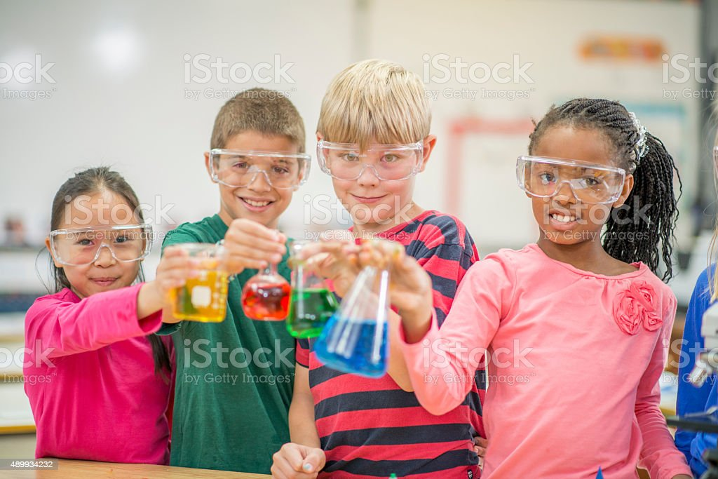 Students Holding Test Beakers with Primary Colors stock photo