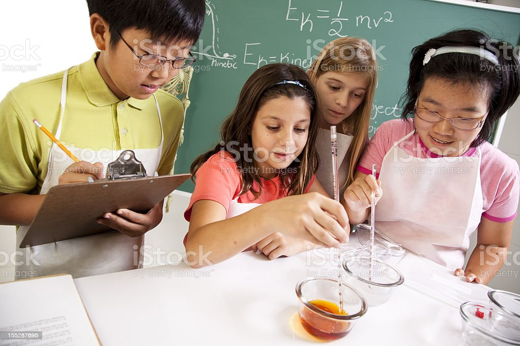Students in biology lab mixing chemicals royalty-free stock photo