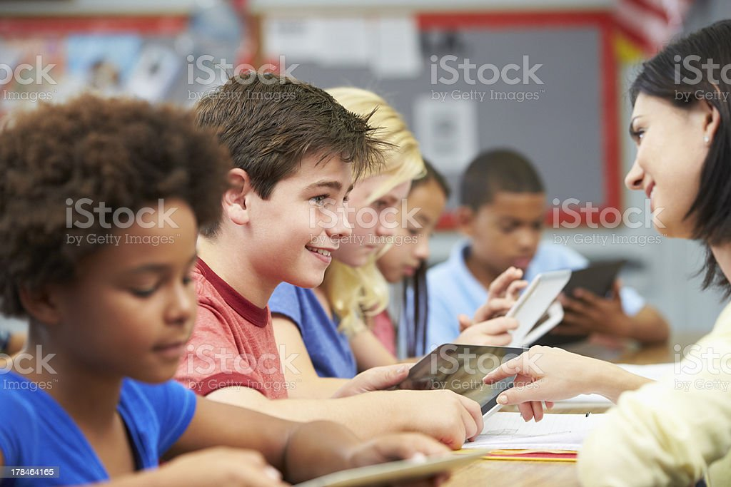 Students in class using digital tablets with a teacher royalty-free stock photo