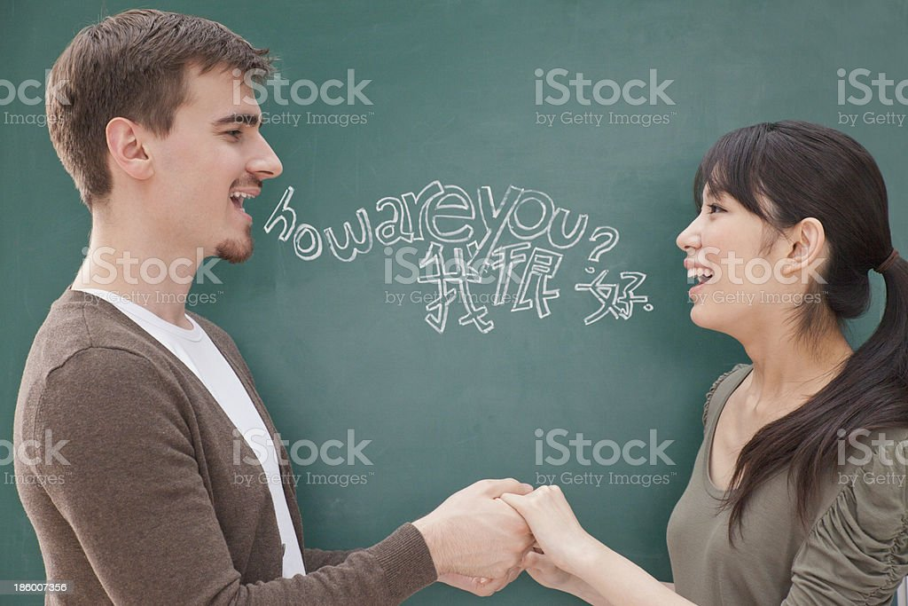 Students in front of chalkboard holding hands stock photo