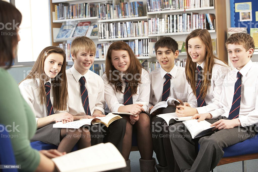 Students In Library Reading Books With Tutor stock photo