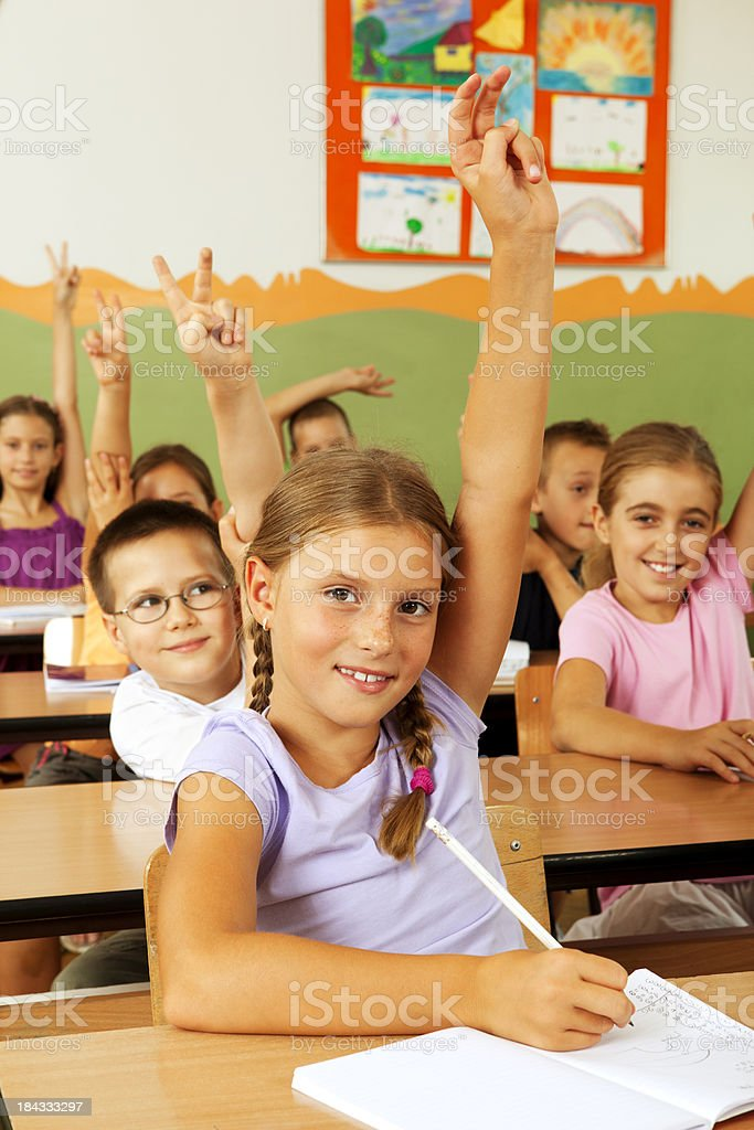 Students in the classroom with arms raised royalty-free stock photo