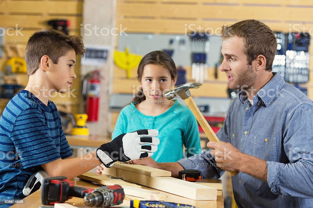 Student's learn about tool safety in woodworking workshop stock photo