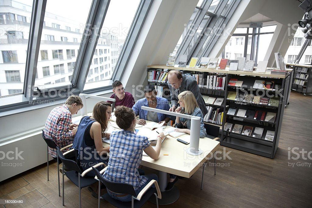 Students learning together with teacher in a library stock photo
