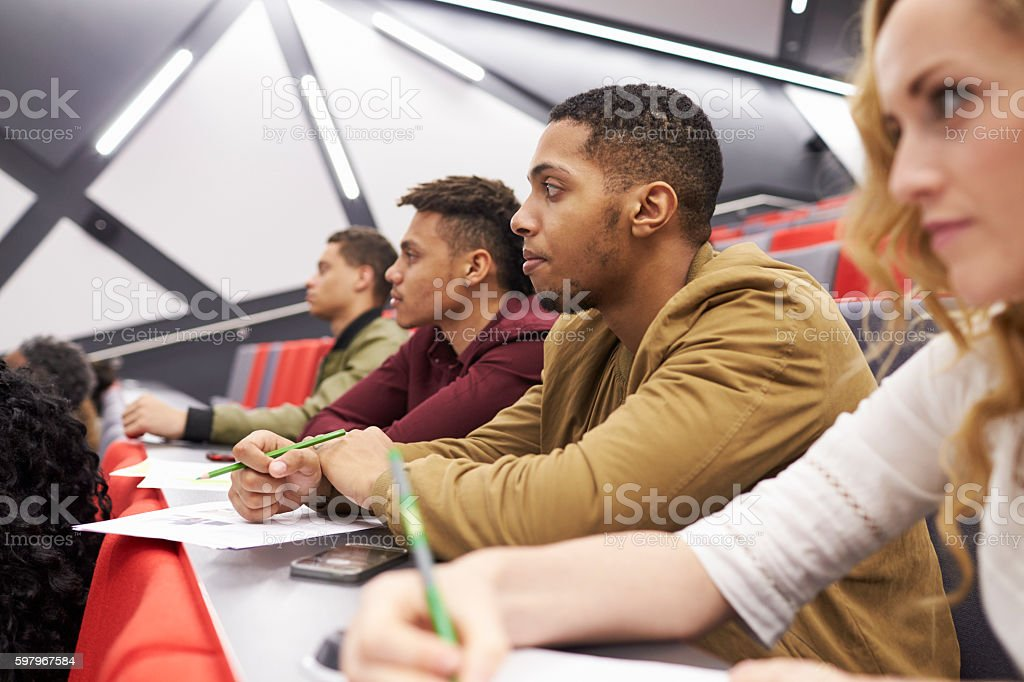 Students listening to lecture at university lecture theatre stock photo