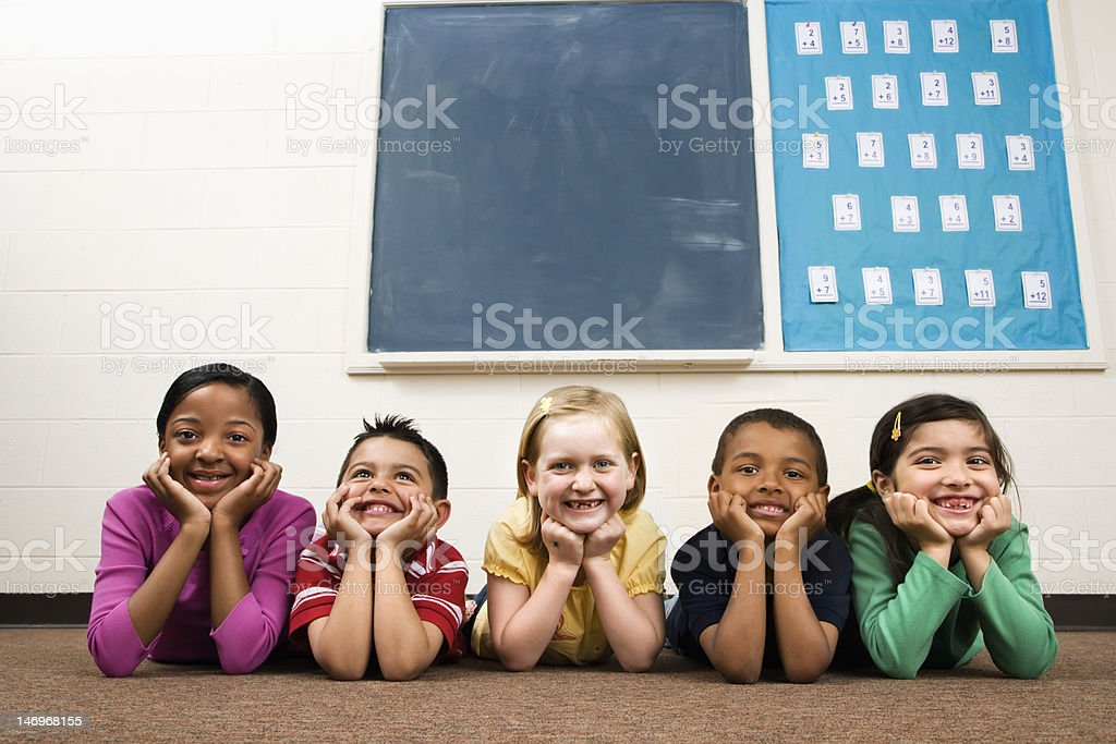 Students Lying on Floor in Classroom. stock photo