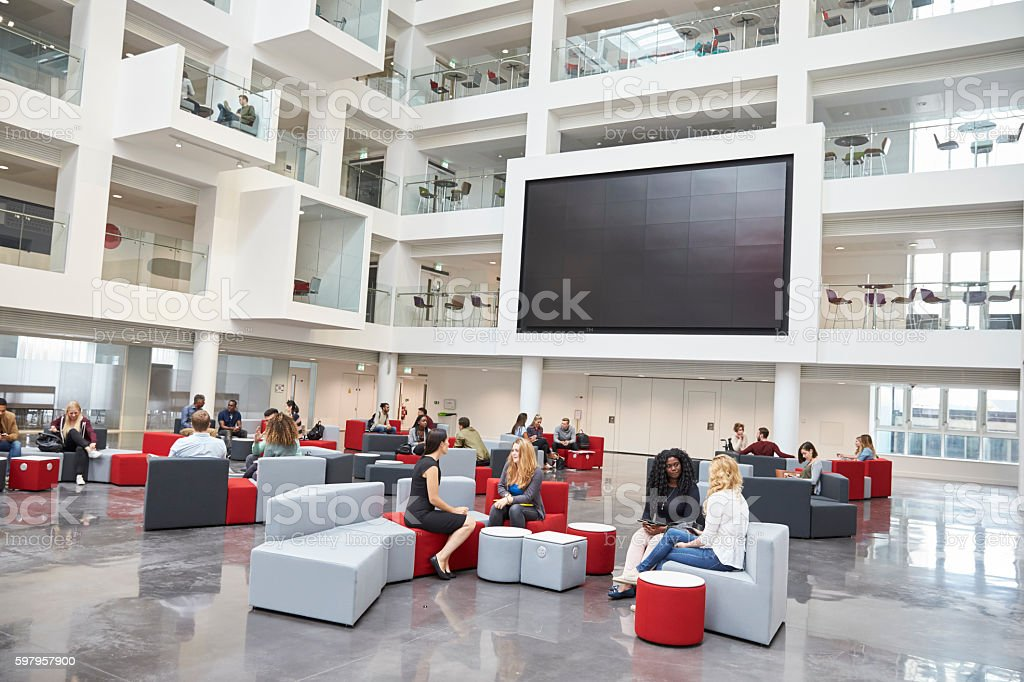 Students meeting in front of screen in atrium at university stock photo