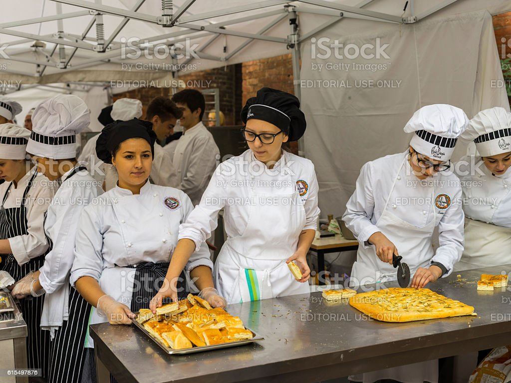 Students of a Piedmontese cooking school preparing focaccia bread stock photo