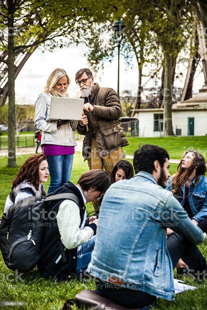 Students on travel in Paris - Tour Eiffel Outdoor lesson stock photo